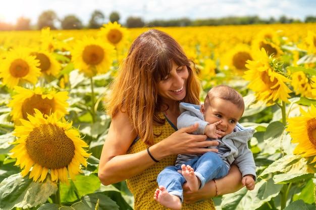 Portret van een blanke moeder en haar baby die lachen in een zonnebloemomgeving, zomerse levensstijl