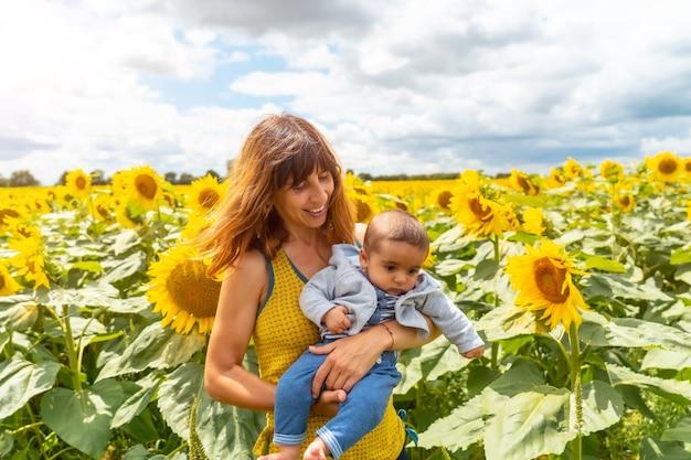 Portret van een blanke moeder en haar baby die plezier hebben in een veld met zonnebloemen, zomerse levensstijl
