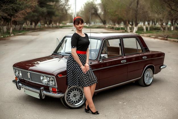 Portret van een blanke mooie jonge meisje in een zwarte vintage jurk, poseren in de buurt van een vintage auto