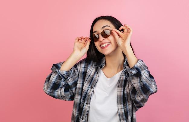 . portret van een blanke mooie vrouw op koraal roze muur met copyspace. stijlvol model. concept van menselijke emoties, gezichtsuitdrukking, verkoop, advertentie, mode, jeugd.