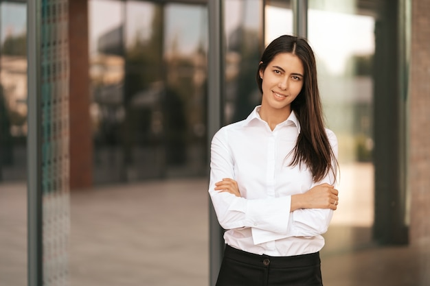 Portret van een blanke, mooie zakenvrouw die lacht en haar handen kruist terwijl ze op het glazen gebouw staat