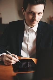 Portret van een blanke ontwerper gekleed in pak en kijkt glimlachend naar de camera terwijl hij een pen voor tablet vasthoudt.