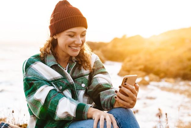 Portret van een blanke opgewonden vrouw die selfie neemt portret op smartphone en glimlacht terwijl ze aan zee zit