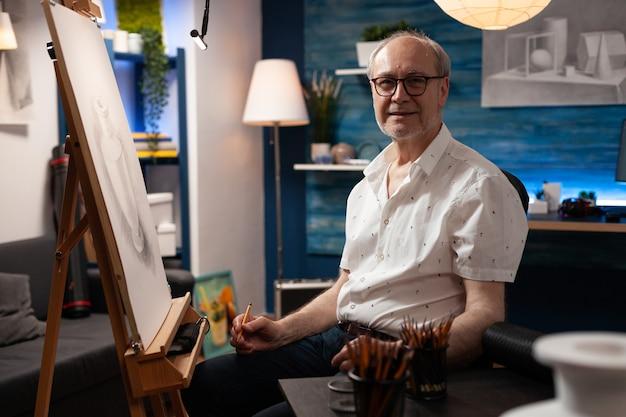 Portret van een blanke oudere kunstenaar die in een kunstwerkstudio zit