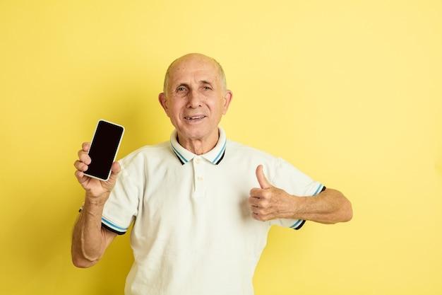 Portret van een blanke senior man geïsoleerd op gele muur