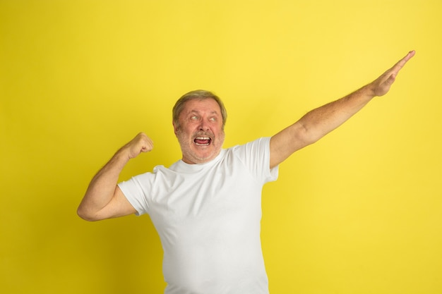 Portret van een blanke senior man geïsoleerd op gele studio muur