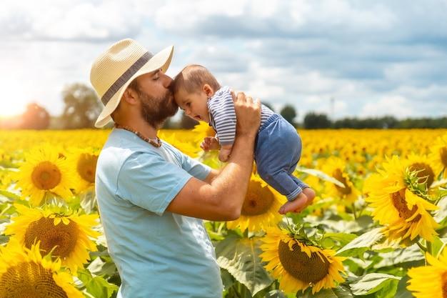 Portret van een blanke vader en zijn baby die plezier hebben in een veld met zonnebloemen, zomerse levensstijl