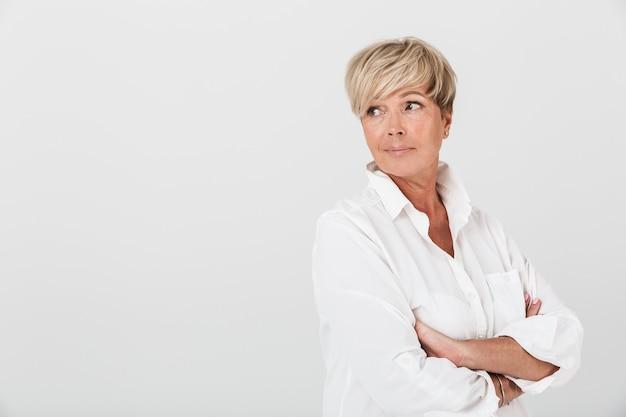 Portret van een blanke volwassen vrouw die naar copyspace kijkt met gekruiste armen geïsoleerd over een witte muur in de studio
