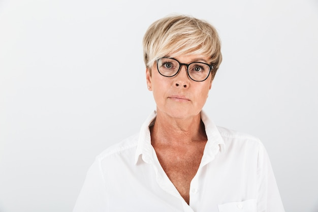 Portret van een blanke volwassen vrouw met een bril die naar een camera kijkt die over een witte muur in de studio is geïsoleerd;