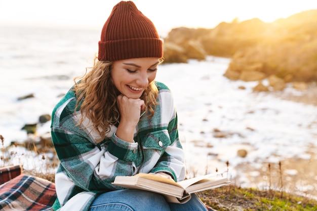 Portret van een blanke vrolijke vrouw die een boek leest en glimlacht terwijl ze op een deken aan zee zit