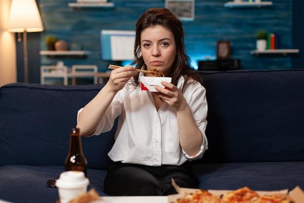 Portret van een blanke vrouw die in de camera kijkt terwijl ze chinese eetstokjes eet, ontspannend op de bank
