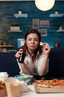 Portret van een blanke vrouw die naar de camera kijkt en een bierflesje in handen houdt