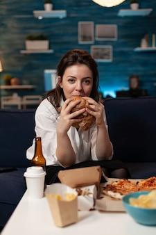 Portret van een blanke vrouw die naar de camera kijkt en ontspant op de bank in de woonkamer