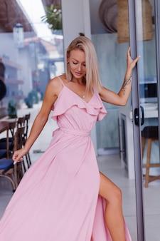 Portret van een blanke vrouw in romantische elegante roze lange jurk op vakantie in luxe rijke villahotel met prachtig uitzicht op tropische palmbomen vrouw in klassieke witte hoed