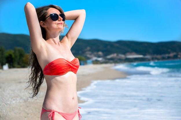 Portret van een blanke vrouw in zonnebril en rode zwembroek met opgeheven handen op het strand