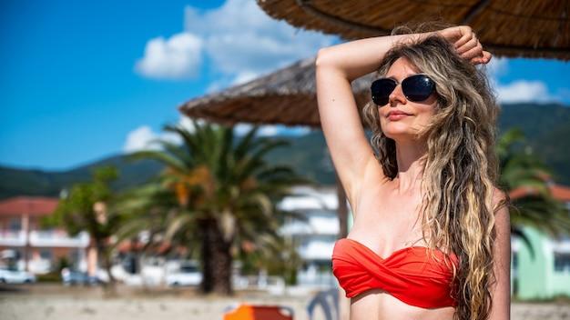 Portret van een blanke vrouw in zonnebril en rode zwembroek op het strand