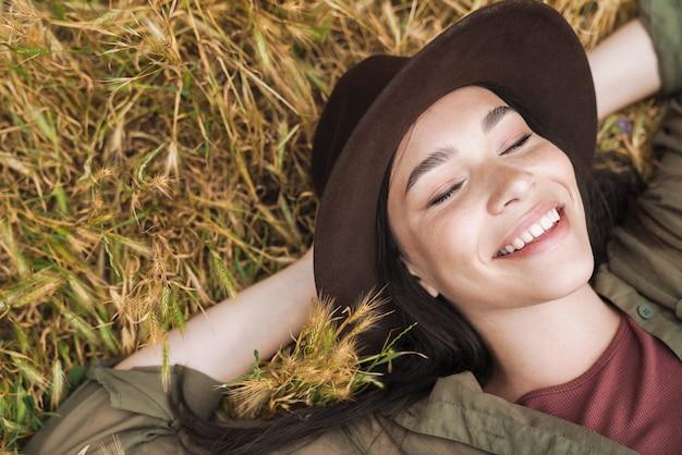 Portret van een blanke vrouw met lang donker haar met een elegante hoed die lacht terwijl ze buiten op het gras ligt
