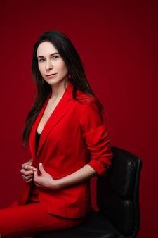 Portret van een blanke vrouw met lang donker steil haar in een rood kantoorpak, zwarte schoenen zit op een zwarte stoel