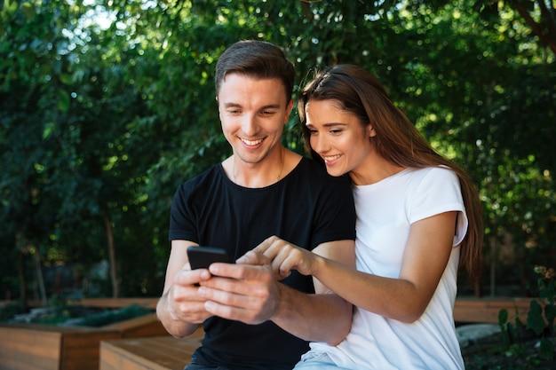 Portret van een blij jong koppel op zoek naar mobiele telefoon