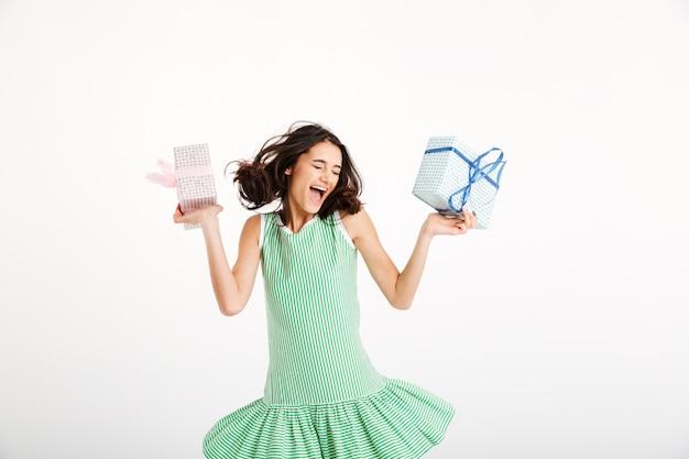 Portret van een blij meisje, gekleed in geschenken met kledingsholding