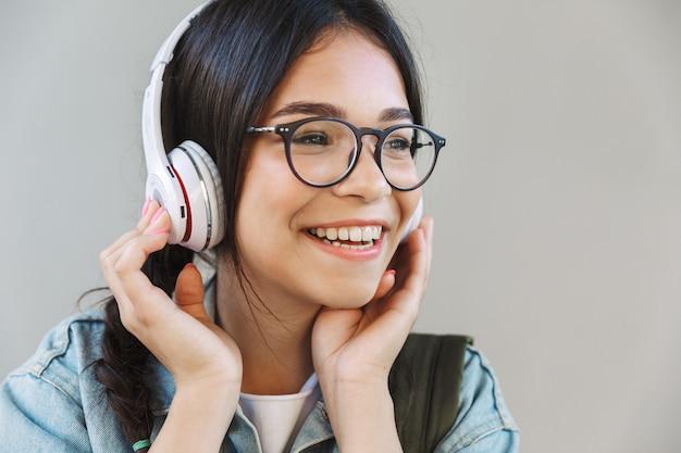Portret van een blij, mooi meisje in een spijkerjasje met een bril die over een grijze muur is geïsoleerd en muziek luistert met een koptelefoon.