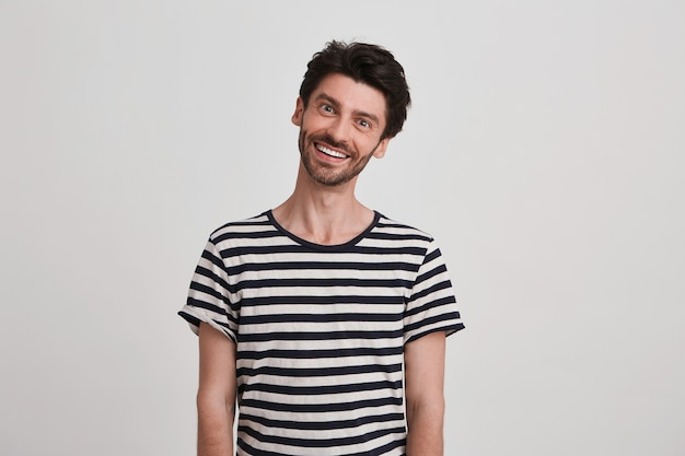 Portret van een blij verrast jonge man met borstelharen draagt een gestreepte t-shirt ziet er speels en gelukkig staan en glimlachen geïsoleerd over witte muur