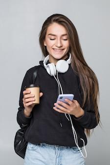 Portret van een blije aantrekkelijke studente die met rugzak aan muziek met hoofdtelefoons luistert terwijl het tonen van het lege scherm mobiele telefoon en dansen geïsoleerd over witte muur