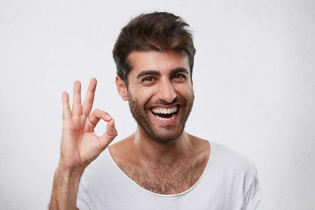 Portret van een blije bebaarde man met stijlvol kapsel dat ok teken toont dat zijn akkoord uitdrukt. jonge knappe zakenman die zijn succes toont en zijn triomf op het werk gebaren verheugt
