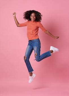 Portret van een blije jonge afrikaanse vrouw in oranje shirt springen en vieren over roze.