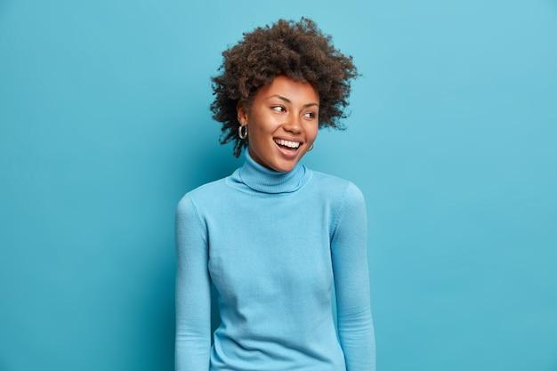 Portret van een blije jonge afro-amerikaanse vrouw glimlacht breed, heeft een vrolijke uitdrukking, draagt een casual blauwe coltrui, draait het hoofd opzij, merkt grappige scène op. monochroom schot. gelukkig emoties concept