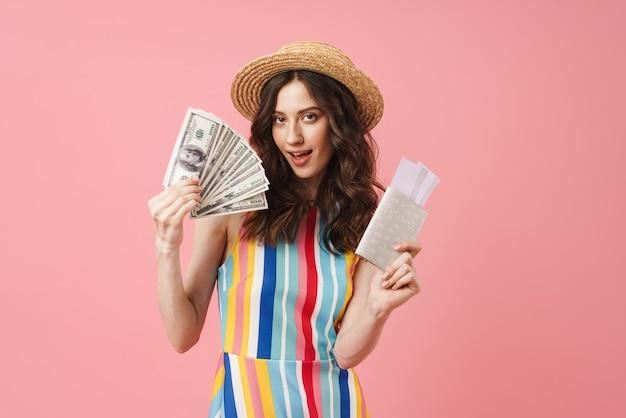 Portret van een blije jonge schattige vrouw die zich geïsoleerd over een roze muur met paspoort met kaartjes en geld