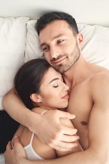 Portret van een blije knappe jonge blanke man met een donkere baard die zijn slapende vrouw in bed knuffelt