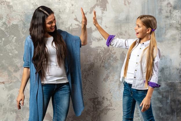 Portret van een blije moeder en dochter die hoogte vijf over grijze achtergrond geven
