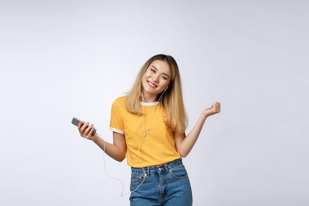 Portret van een blije tevreden aziatische vrouw in koptelefoon luisteren naar muziek en springen