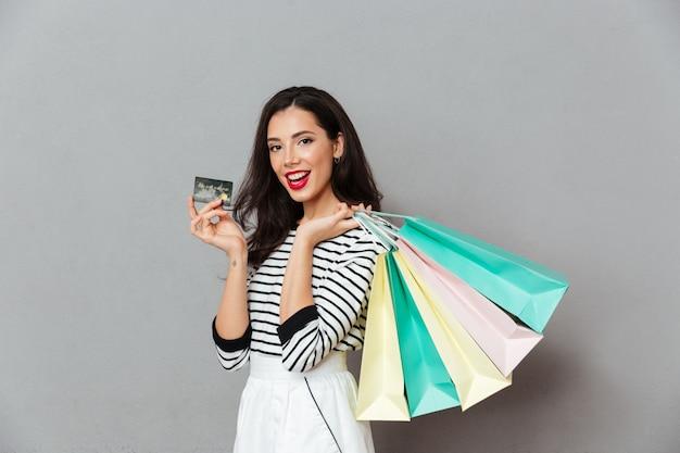 Portret van een blije vrouw die creditcard toont