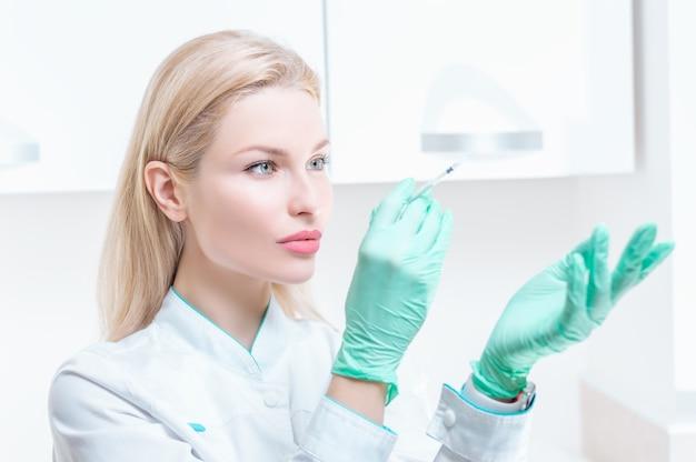 Portret van een blond meisje in een medische jurk met een spuit in haar handen. advertentie medisch centrum. gemengde media