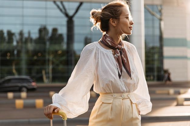 Portret van een blond meisje in een witte blouse, een beige broek, een bruine zijden sjaal en een bril die bagage vasthoudt en in de verte kijkt