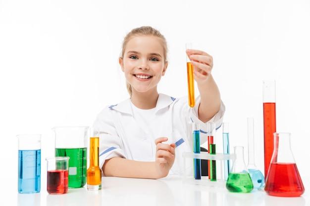 Portret van een blond meisje in een witte laboratoriumjas die chemische experimenten maakt met veelkleurige vloeistof in reageerbuizen geïsoleerd over een witte muur