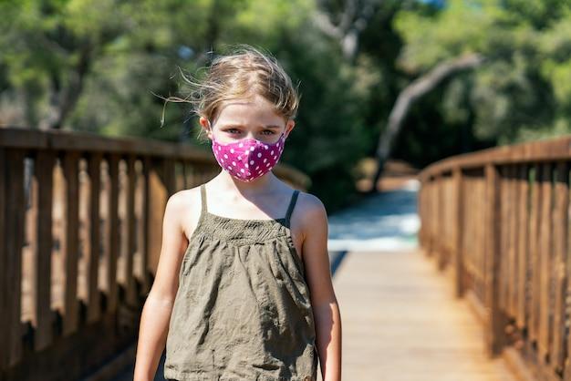 Portret van een blond meisje met blauwe ogen met een gezichtsmasker op vakantie op een houten brug met pijnbomen met een ernstig gezicht in een groene jurk midden in de coronavirus-pandemie