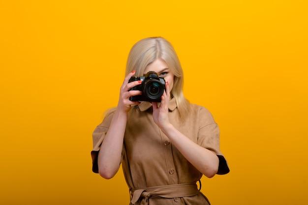 Portret van een blond meisje met een camera in hand op geel