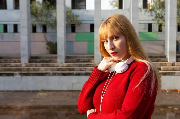 Portret van een blond meisje met rode lippenstift en rode trui, luisteren naar muziek met een koptelefoon in het park.