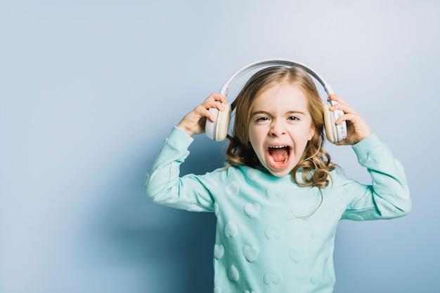 Portret van een blond meisje met witte hoofdtelefoon op haar hand schreeuwen