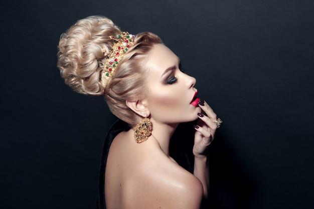 Portret van een blond model dat een kroon en inkomsten draagt, haar lippen met hand over een zwarte achtergrond aanraakt