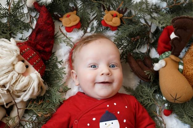 Portret van een blonde baby met kerstmisspeelgoed Premium Foto
