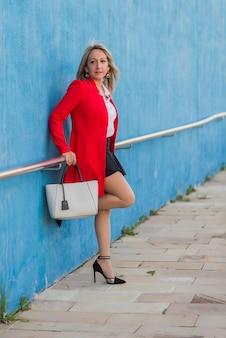 Portret van een blonde elegante vrouw die rood jasje draagt dat op een metaalomheining op een muur leunt