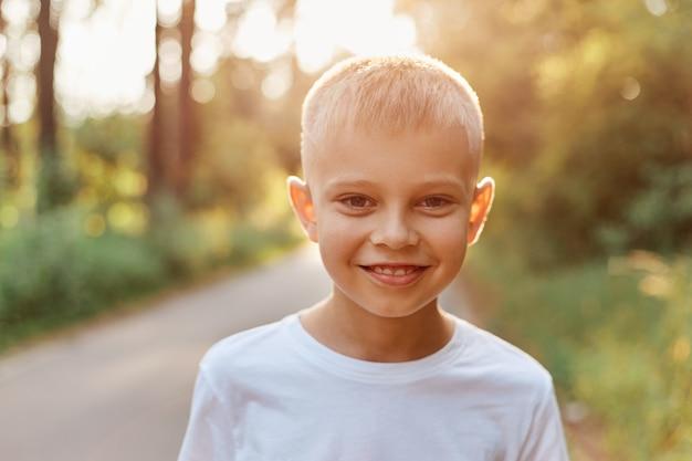 Portret van een blonde gelukkige kindjongen buiten op warme zonnige zomerdag, gekleed in een wit casual t-shirt, camera kijkend en positieve emoties uitdrukkend.