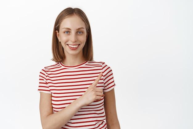 Portret van een blonde gelukkige vrouw die lacht, met de vinger naar de rechterbovenhoek wijst, met een kortingspromo voor de verkoop, productplaatsing, staande tegen een witte muur