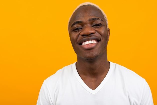 Portret van een blonde glimlachende charismatische afrikaanse zwarte man in een wit t-shirt op oranje