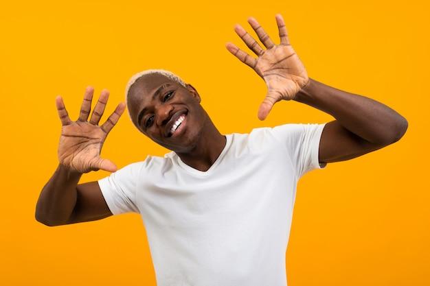Portret van een blonde glimlachende charismatische afrikaanse zwarte mens die handen aan de kanten in een witte t-shirt op een oranje studioachtergrond besluipt