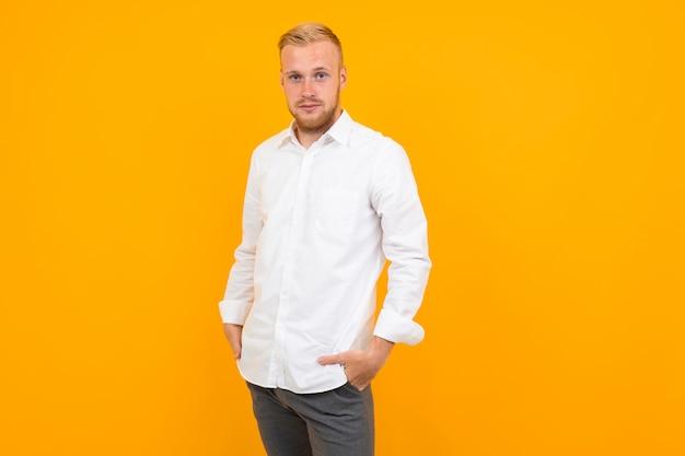 Portret van een blonde jonge man in een wit overhemd op geel met kopie ruimte